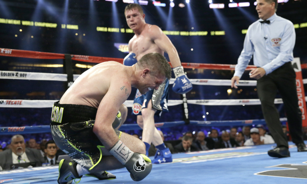 Liam Smith, left, falls to the mat after taking a body shot and being knocked out buy Canelo Alvarez fight during the ninth round of the WBO Junior Middleweight Championship boxing match at the stadium in Arlington, Texas, Saturday, Sept. 17, 2016. (AP Photo/LM Otero) ORG XMIT: TXMO104